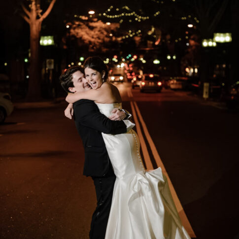 The bride looks over her shoulder as her new groom swoops her up into his arms in the middle of the street of downtown Greenville, SC.