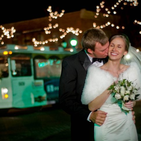 A groom kisses his new bride on the cheek with the classic Greenville trolley in the background.