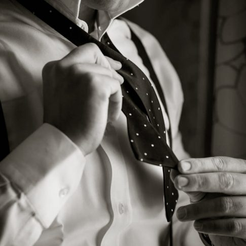 A groom takes care in tying his bowtie in preparation for his upcoming nuptials.