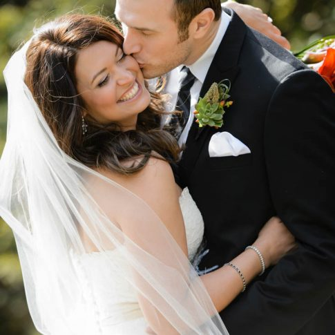 The groom plants a loving kiss on the cheek of his new wife moments after the wedding ceremony.