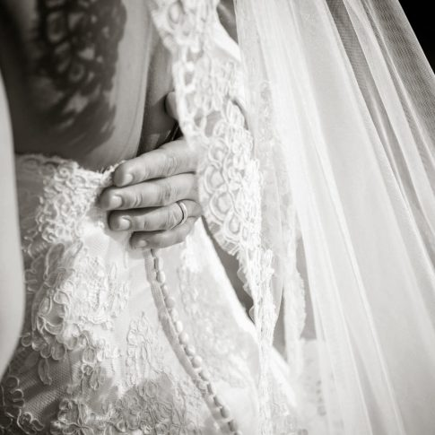The grooms hand, featuring his new wedding ring, rests on his wife's back.