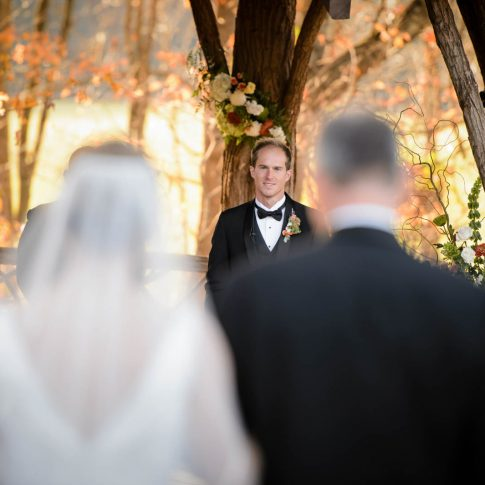 The groom smiles in anticipation as he sees his bride walking down the aisle towards him.