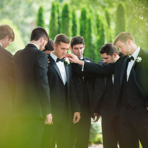 Groomsmen lay hands on the groom in prayer as they prepare for the upcoming wedding ceremony.