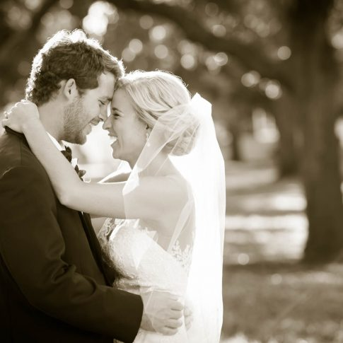 Sepia image of bride and groom embracing and laughing