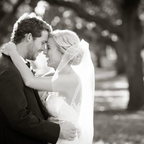 A black and white photograph of newlyweds embracing and laughing.