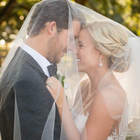 With the tulle veil resting on both the bride and groom, the bride gazes happily up at her new husband.