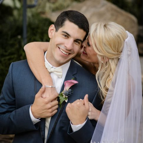 The groom smiles as he faces the camera and holds the hands of his bride who sweetly snuggles her face next to his.