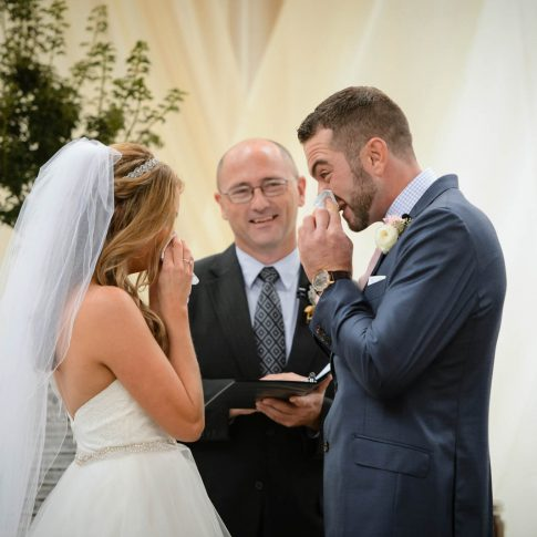 A bride and groom wipe their noses with tissue during their wedding ceremony.