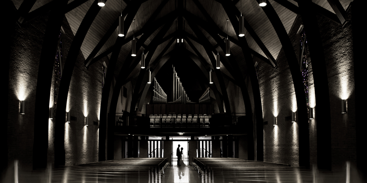 A bride and groom are silhouetted in an overall image of the Westminster Presbyterian Church at night.