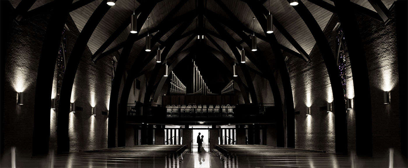 A bride and groom are silhouetted in an overall image of the Westminster Presbyterian Church in Greenville, SC at night.
