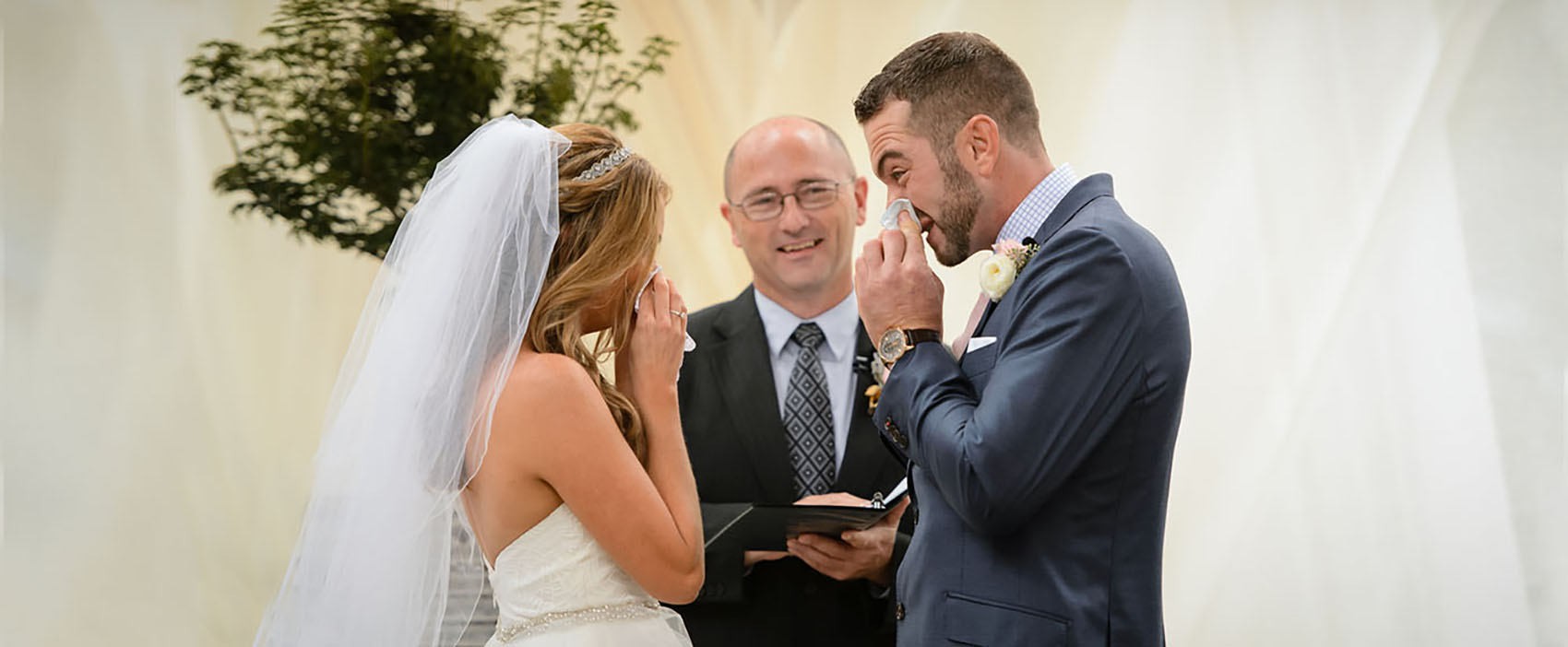 A bride and groom wipe their noses with tissue during their wedding ceremony the Wyche Pavilion in Greenville, SC.