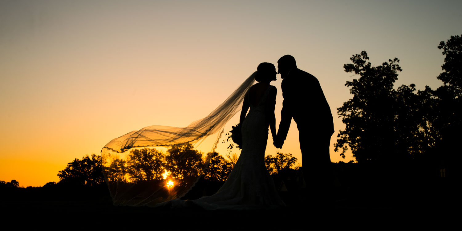 We always strive to create at least one silhouette shot of the bride and groom on their wedding day. It is a timeless and simple photograph that they can appreciate for the artistry in addition to it being a personal and special moment. And a silhouette photograph is actually one of my favorite photos my parent's wedding photographer took on their wedding day. This image was created on Brock and Jared's wedding at Cross Creek Plantation in Seneca, SC--about a 45 minute drive from Greenville. The green lawn behind the country club overlooks the golf course and setting sun is a favorite location of ours for wedding photographs. The bride and groom are holding hands and leaning in for a kiss as the wind catches the brides lace lined veil. You can see the round orange glowing sun sinking over the horizon behind the trees. We got down low to the ground so that we could photograph the bride and groom in the orange and yellow twilight sky.