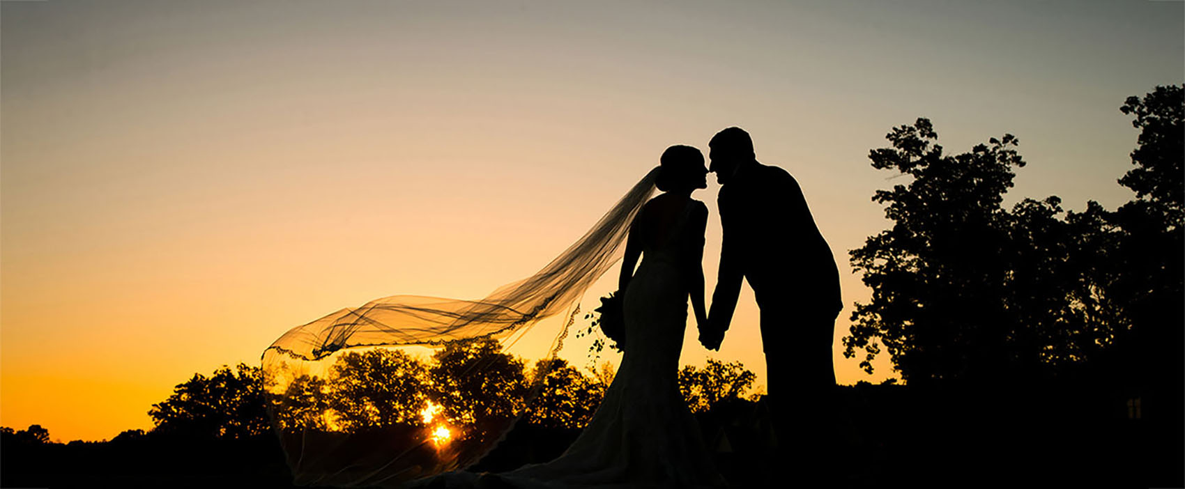 Silhouette of a bride and groom about to kiss at sunset.