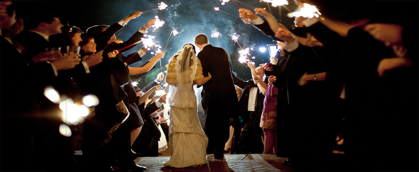 A bride and groom exit their wedding reception through the path lined with guests holding sparklers.