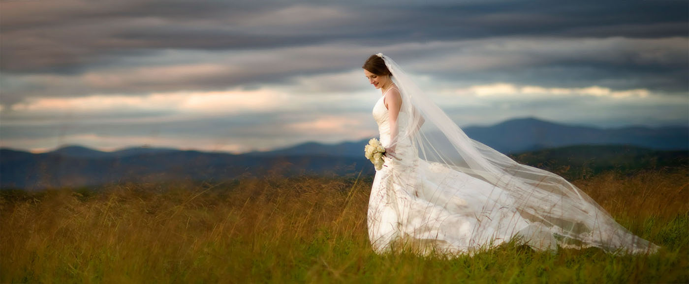 The bride is walking through a hayfield with the Blue Ridge Mountains in the background.