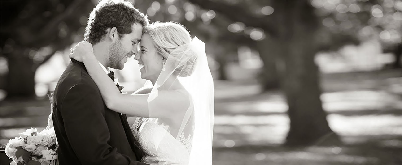 The bride and grooming hug and laugh in this black and white toned photo.