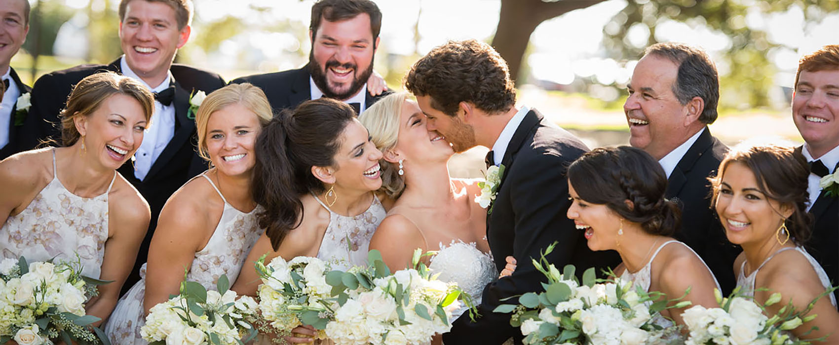 Bride and groom hug and kiss surrounded by wedding party laughing and smiling.