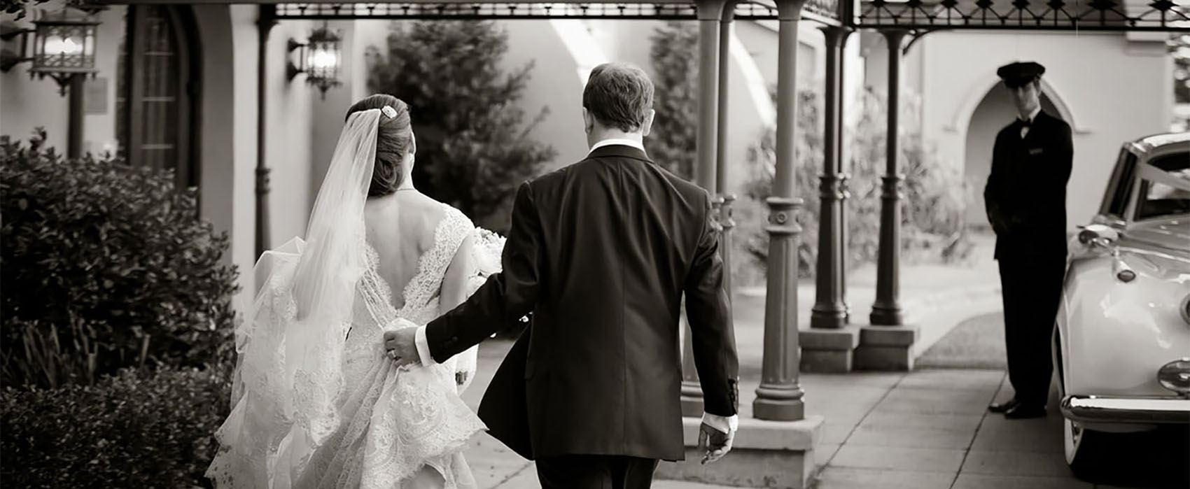 A bride and groom walking to their awaiting chauffeur and Rolls-Royce.