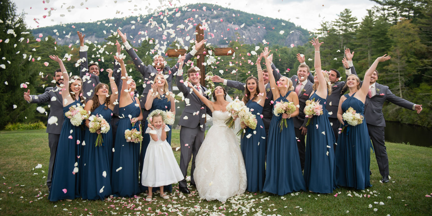 Weddings are such a joyous time. We are so lucky to be a part of the happiest day of people's lives, and this image captures that perfectly. This exquisite wedding party of bridesmaids in a smokey dark blue floor length dresses and groomsmen in grey suits with pick ties and really having fun. Everyone grabbed a handful of pink and white rose petals, courtesy of Sandy at Fiddlehead Designs--who also provided the stunning bouquets, and at the count of three they all threw fistfuls of petals into the air. The petals floated down like snow flakes around the group, showering them all. And my very favorite part of this image is the little flower girl, donning a baby's breath flower crown, is smiling and busting with so much excitement that she closes her eyes and clasps her hands tightly by her cheeks. And can you image a more picturesque setting for a wedding. Elizabeth and Rowdy were married at High Hampton Inn in Cashiers, NC. A resort nestled in the Blue Ridge Mountains, about an hour and a half drive west of Asheville. The rustic resort's main inn and private cabins are situated around a private lake edged by a rock faced mountain in the background. Shortly after this image was taken, we all walked to the reception across the property to the pavilion to dance the night away with Steel Toe Stilettos.