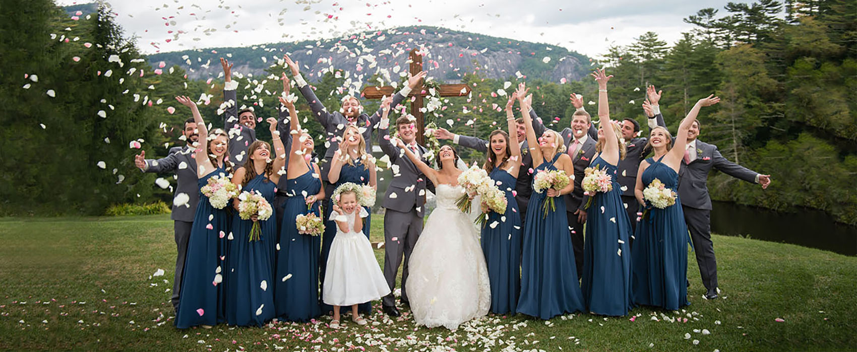 A wedding party grabs a handful of pink and white rose petals and threw them into the air in celebration.