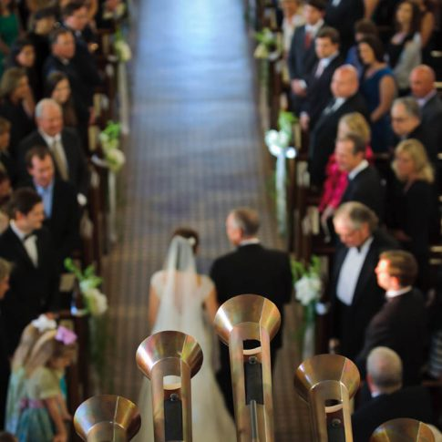 A detail shot of the horns in a chapel as they play while the bride and her father proceed down the aisle.