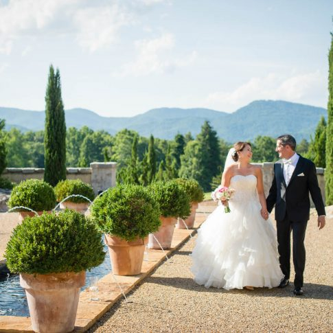 A bride and groom join hands as they take a stroll around the fountains of Hotel Domestique in Travelers Rest, SC.