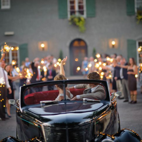 A bride and groom wave goodbye to their guests who are waving sparklers as they drive away from their reception at Hotel Domestique.
