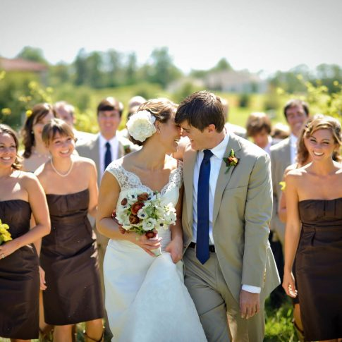 A bride and groom lean in for a kiss as their wedding party looks on in laughter while walking through the vineyards of Hotel Domestique.