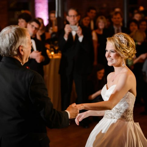 The bride happily smiles at her father mid-twirl during their father-daughter dance.