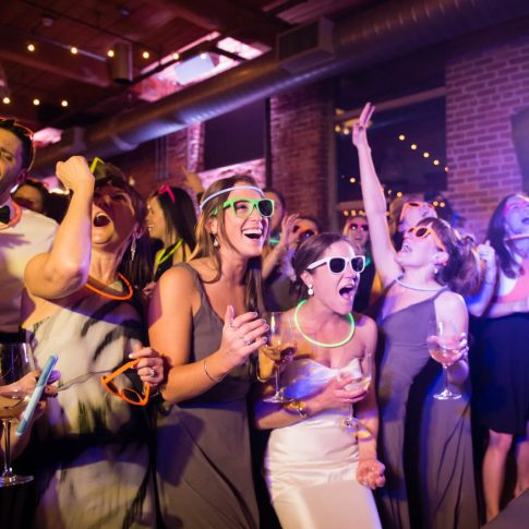 The bride, accompanied by her bridesmaids and guests, dance excitedly to the music of the live band during a wedding reception at the Wyche Pavilion in Greenville, SC.