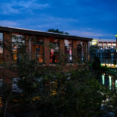 A shot of the Certus Loft featuring the new husband and wife sharing a kiss while the loft overlooks the Reedy River at night.
