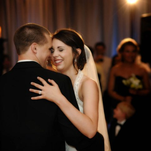 During a first dance in the Hyatt Hotel in Greenville, SC a bride and groom share a moment of laughter.