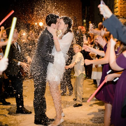In the midst of being showered by white confetti, a new husband and wife share a quick kiss in the midst of their guests as they prepare to depart for their honeymoon.