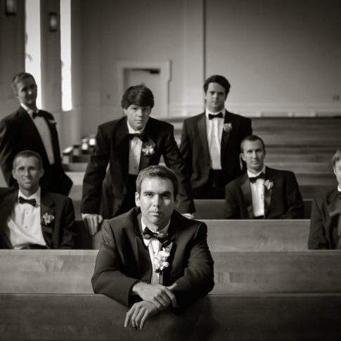 The groom gazes at the camera while his groomsmen line the pews behind him.