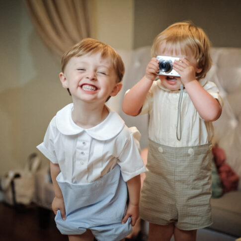 Two young boys at a wedding reception are filled with joy as one excitedly grins at the camera while another holds a small camera up to his eyes to take a photo.