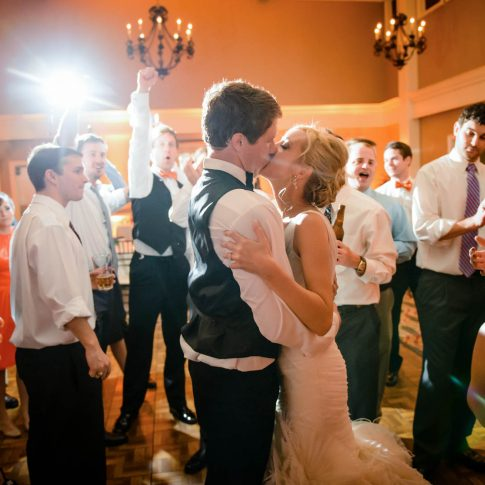 Newlyweds kiss at the end of their reception as the wedding party looks on and cheers.