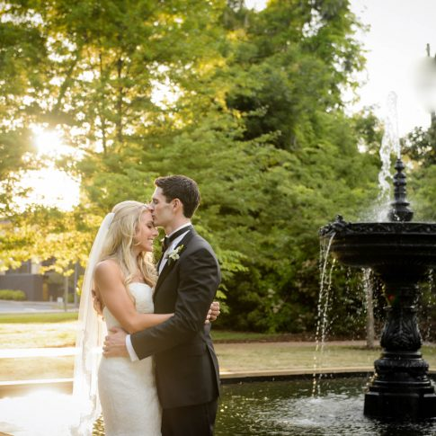 Husband kisses his new wife on the forehead beside the fountain at the Piedmont Club.