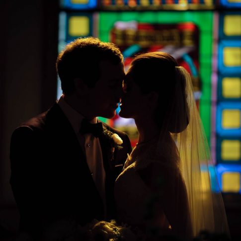A new husband and wife share a kiss with the stained glass of the chapel they were wed in shining behind them.