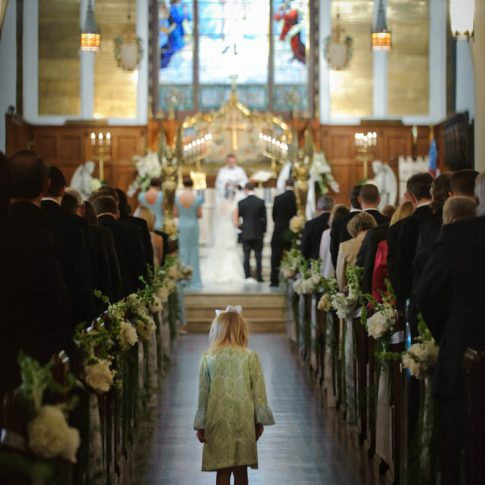A younger guest at the wedding prays as she stands in the middle of the aisle.