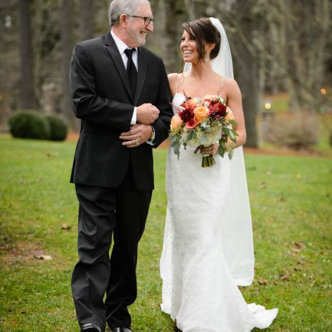 The bride laughs as she is escorted by her father.