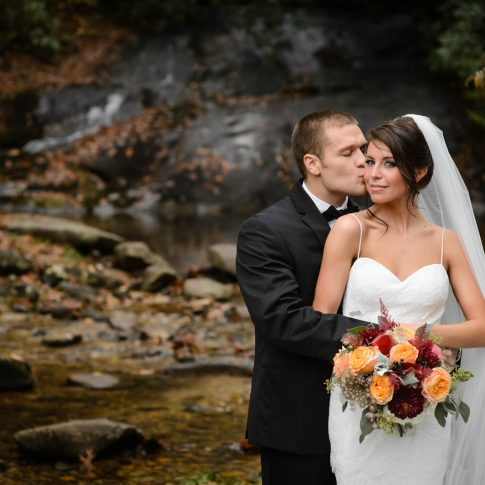 The bride softly glances at the camera as her groom kisses her cheek while they stand embraced in front of a waterfall in Lonesome Valley in Cashiers, NC.