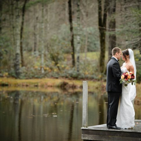 Standing on the dock overlooking the pond at Lonesome Valley in Cashiers, NC, newlyweds share a loving gaze.