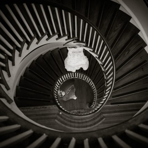 A lace wedding gown hangs in the circular staircase at Lowndes Grove Plantation.