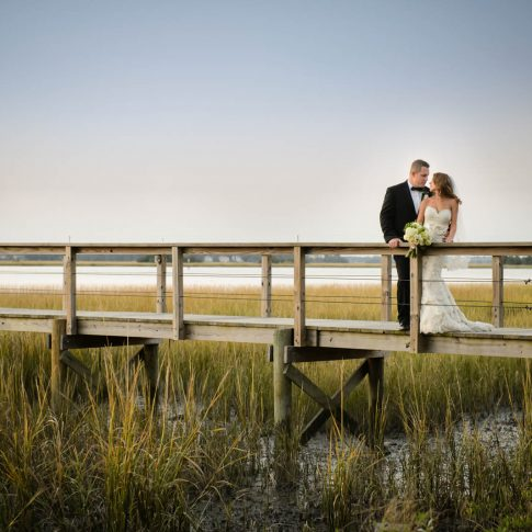 The bride looks back at her groom as they stand on a pier in Lowndes Grove overlooking the marsh.