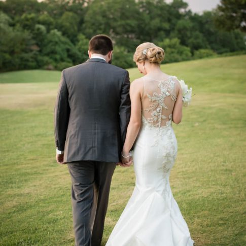 A bride and groom walk hand-in-hand over the golf course at the Madren Center in Clemson, SC.