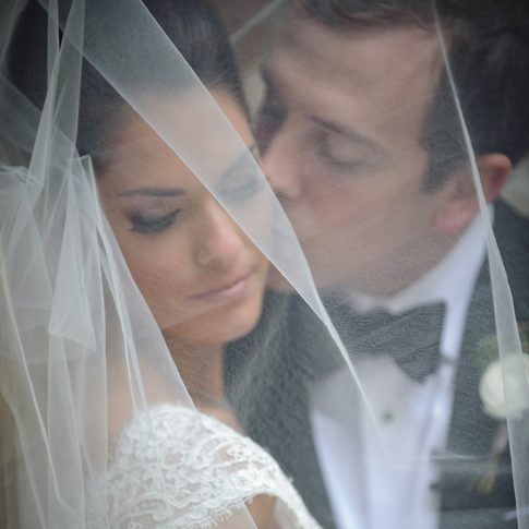 A bride and groom snuggle under her veil as the groom kisses the bride's cheek.