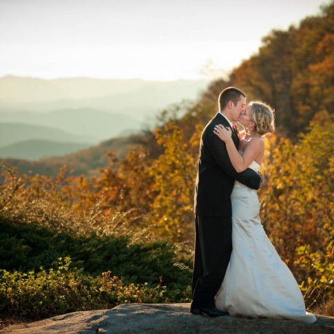 A bride and groom kiss while standing on a rock on Glassy Mountain.