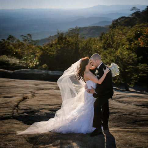 The bride and groom softly embrace as they stand on a rock overlooking the mountains at the Cliffs at Glassy.