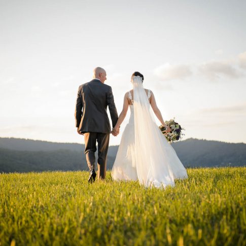 A groom looks happily at his new wife as they walk through a field in the mountains of Asheville, NC.
