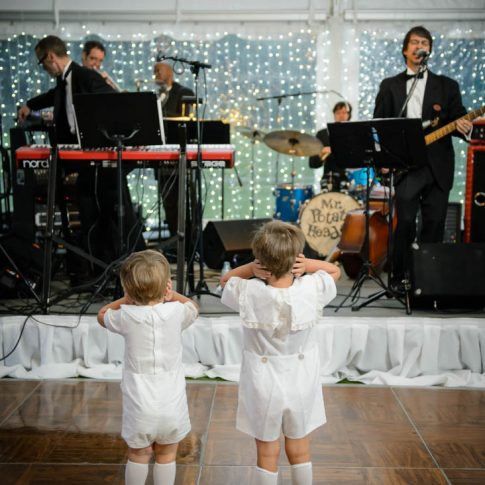 Two young boys stand on the dance floor facing the band and covering their small ears to ease the volume of the music.